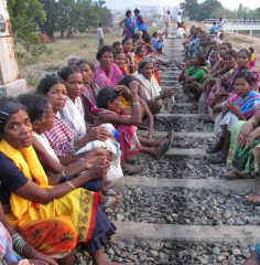 Women sit on the tracks, with the factory behind.