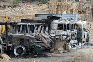Burned vehicles are seen at the 'Hellas Gold' mining company's facility in the village of Skouries
